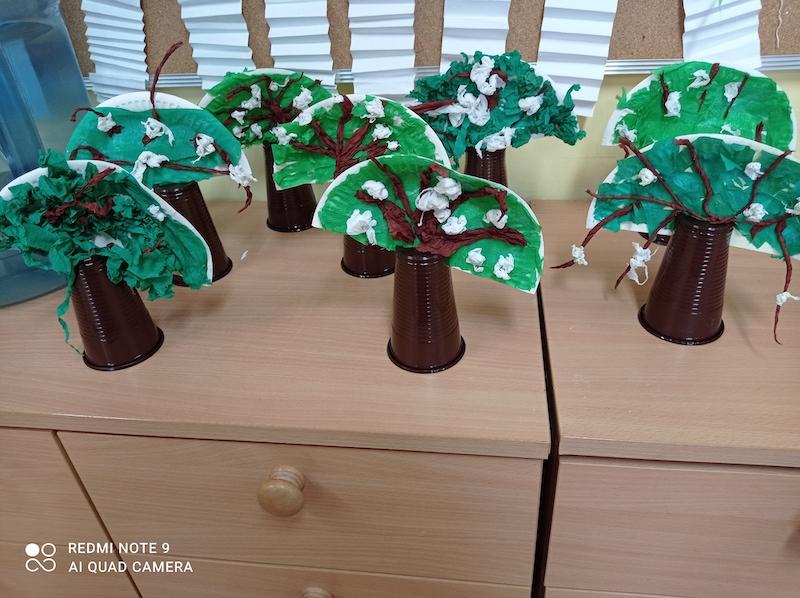 Prace uczniów przedstawiające drzewa wykonane z plastikowych kubeczków i papierowych talerzyków.