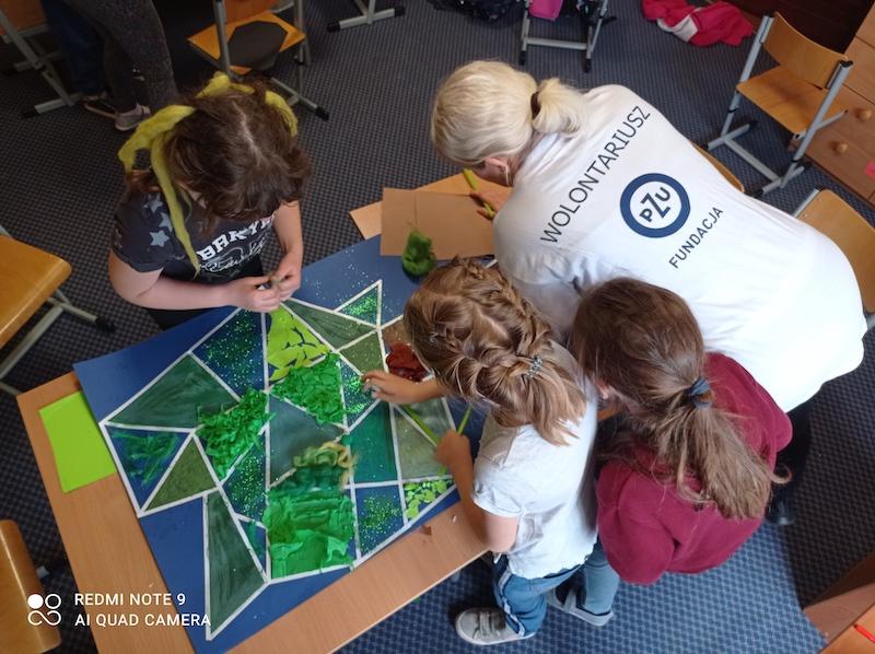 Uczniowie oddziału II D wykonują drzewo złożone z geometrycznych figur przy użyciu różnych materiałów plastycznych.