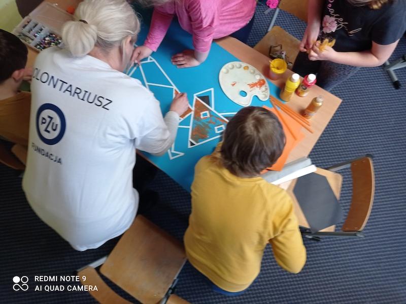 Wolontariusz PZU pomaga dzieciom pokolorować geometrycznego lisa.