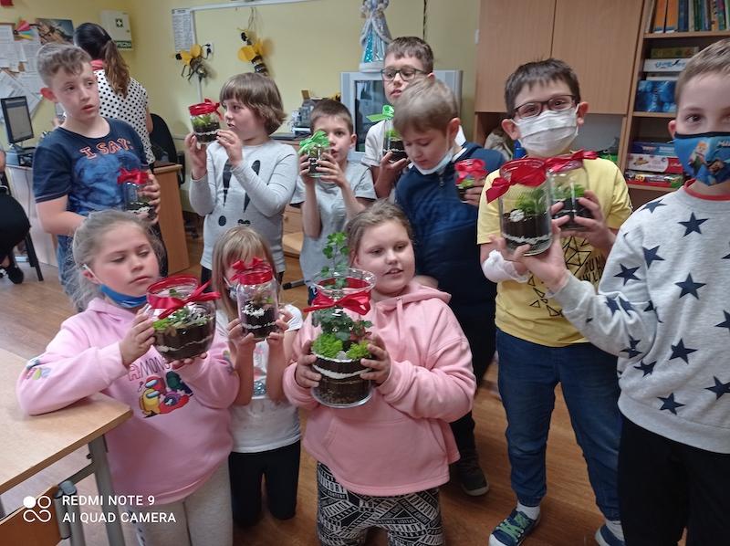 Uczniowie oddziału II D pozują do zdjęcia trzymając w dłoniach prezenty (las w słoiku) dla mamy z okazji jej święta.
