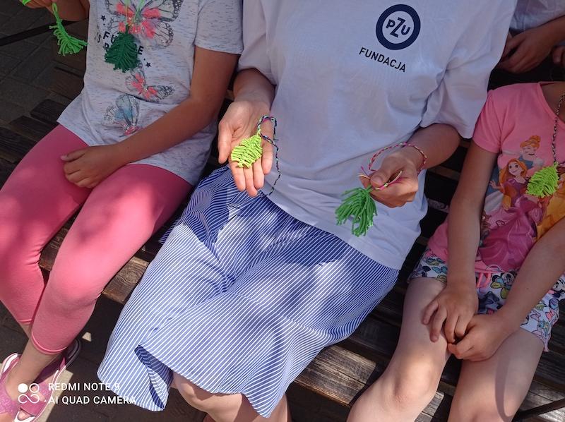 Uczennice  i wychowawca świetlicy prezentują naszyjniki wykonane techniką makramy.