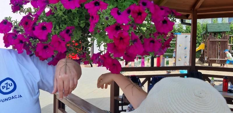 dziewczynka i wolontariusz Fundacji PZU trzymają na rękach patyczaki
