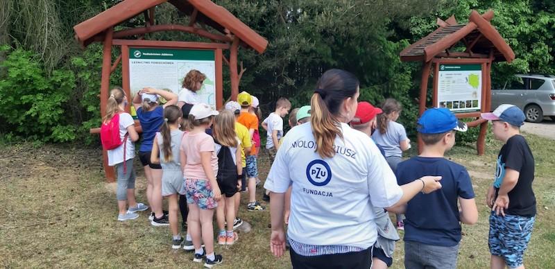 dzieci i wolontariusz Fundacji PZU stoją przed tablicą w lesie