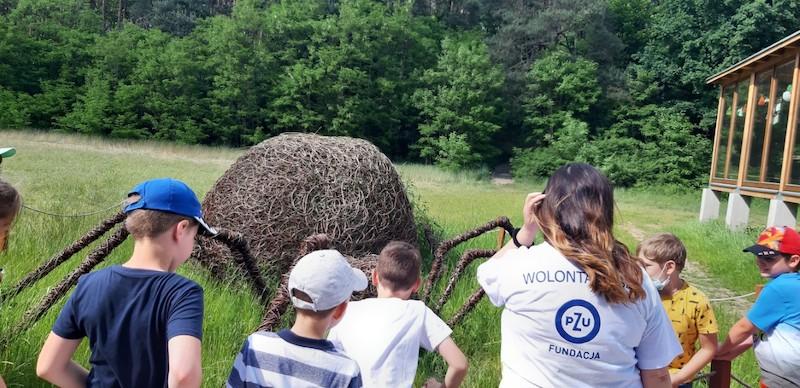 wolontariusz PZU wraz z dziećmi przygląda się dużemu pająkowi