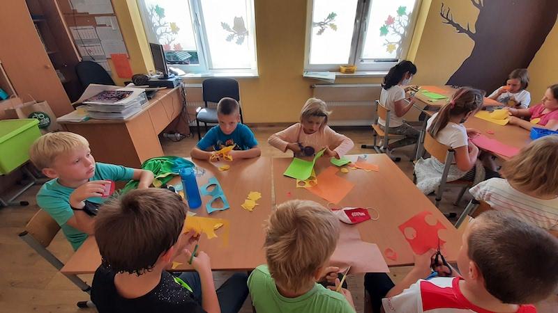 Zdjęcie przedstawia uczniów wycinających kolorowe kropki.
