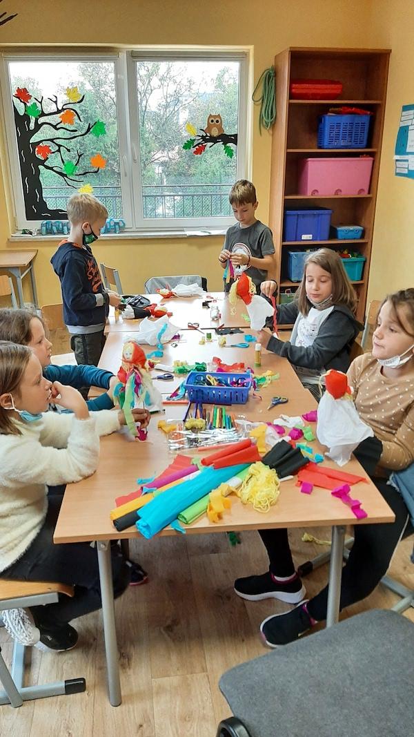 Zdjęcie przedstawia uczniów wykonujących kukiełkę z krepiny i włóczki.