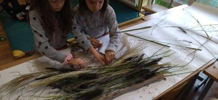 Zdjęcie pokazuje jak dzieci tkają wątek, czyli trawa, suszone kwiaty mech, szyszki.
