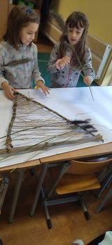 Zdjęcie przedstawia uczniów którzy wykonali krosna w kształcie trójkąta, osnowa to sznurek jutowy.